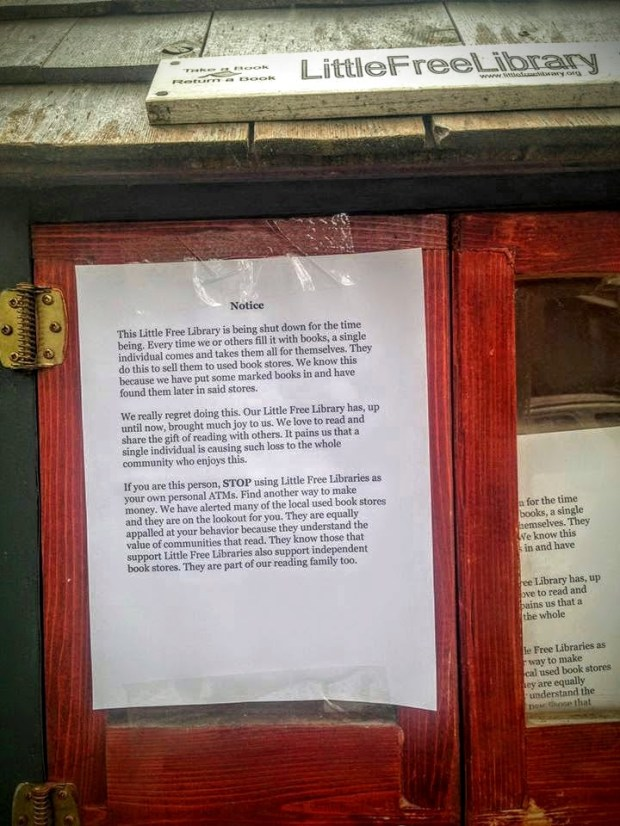 Bethany Gladhill and Patrick Rhone of St. Paul left this sign on their Little Book Library after the cubbie was cleaned out by thieves more than a dozen times in recent weeks. (Pioneer Press: Julio Ojeda-Zapata)