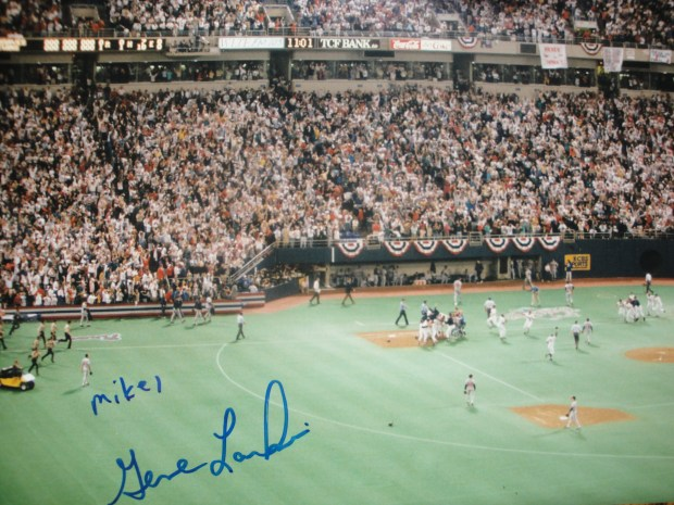 """Fifteen nanoseconds of fame (responsorial) ... Writes JOHN IN HIGHLAND: """"Like Poet X of PDX [BB, 10/15/2016], I had the chance to meet Gene Larkin, hero of Game Seven of the '91 World Series. [Bulletin Board interjects: Jack Morris, among others, might quibble with that description. ONE of the heroes of Game Seven? Yes!] Our seats for the game were in the far reaches of the second deck in left-center field. I took this photo of the mob scene around Larkin at first base as the celebration of his game-winning hit began. I had to wait until the one run was flashed up on the scoreboard. You can see the two empty seats on the aisle behind the Braves' dugout, from which Ted Turner and Jane Fonda had just beaten a hasty retreat. The large white sheet hanging over the front of the second deck says 'Hrbek's Hanky.' Dan Gladden and Jack Morris (blue jacket) are running down the first-base line toward Larkin. The Larkin hit came at exactly 11 p.m., so that means that it occurred at the 'Stroke of Midnight' for the Braves' fans back in Atlanta! ... The next year, I took my kids to Twins Fest. Larkin was doing a 'signing' session. We had brought along copies of the picture for Gene to sign, along with an extra copy for him. I'm sure that he had already received many great photos that were better than ours, but he thanked us and impressed us with his sincerity."""""""
