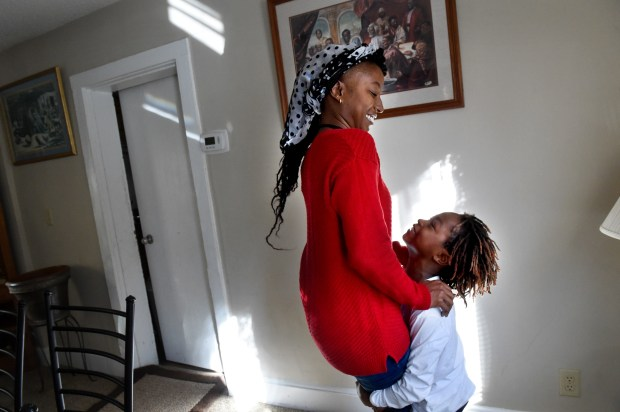 "Alisha Noel gets lifted up by her son, Camden, in St. Paul on Thursday, Oct. 20, 2016. Noel worked three jobs to save $25,000, got pre-approved for a bank loan for $175,000, found a house she loved -- the one that she grew up in, in the old Rondo neighborhood. Then everything fell apart and she lost every penny of her savings along with the house. ""I was embarrassed and I was hurt but I had to face my fear and reject it in order to move forward,"" she said. (Pioneer Press: Jean Pieri)"