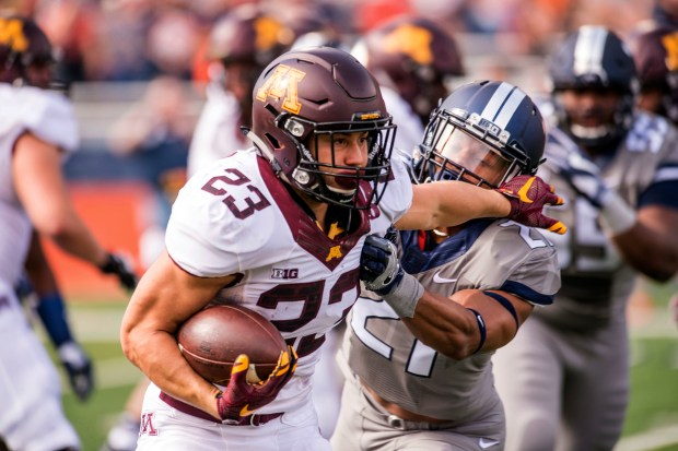 Illinois defensive back Patrick Nelson (21) tries to tackle Minnesota running back Shannon Brooks (23) during the second quarter of an NCAA college football game Saturday, Oct. 29, 2016, at Memorial Stadium in Champaign, Ill. (AP Photo/Bradley Leeb)