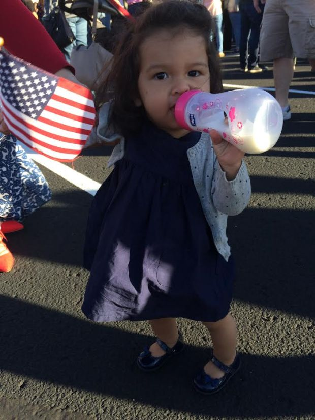 Someone in the crowd gave an American flag to Rosa, 14 months, who was outside the Donald Trump rally on Sunday, Nov. 6, 2016, with her parents, Shuo Wang and Sofia Lopes of Vadnais Heights. (Pioneer Press photo)