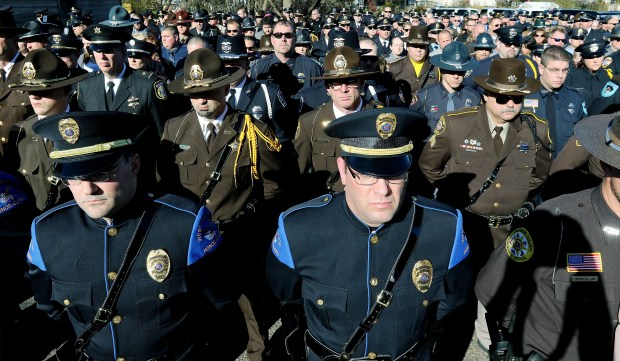 Law enforcement officials stand at attention after a service for Rusk County Deputy Sheriff Dan Glaze Jr., Friday, Nov. 4, 2016 at the former Cameron Elementary School in Cameron, Wis. Douglas Nitek is accused of killing Glaze Saturday night, Oct. 29, as the officer investigated a report of a suspicious vehicle in a field several miles from the suspect's residence near Ladysmith, about 130 miles northeast of Minneapolis. (Dan Reiland/The Eau Claire Leader-Telegram via AP) MANDATORY CREDIT