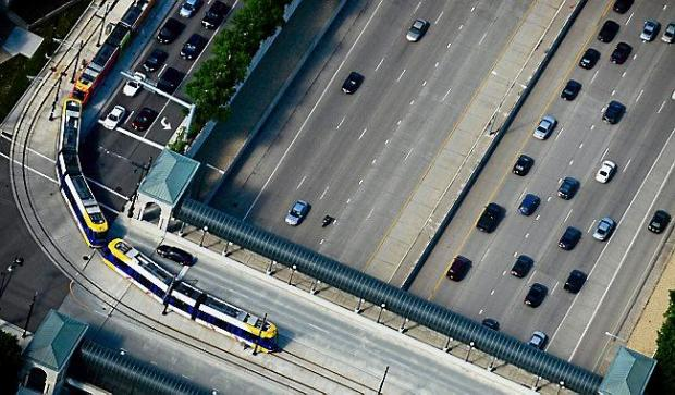 The Green Line light rail train turns onto Cedar Street over I-94 in this aerial photo taken on Friday, June 20, 2014. (Pioneer Press: Ben Garvin)