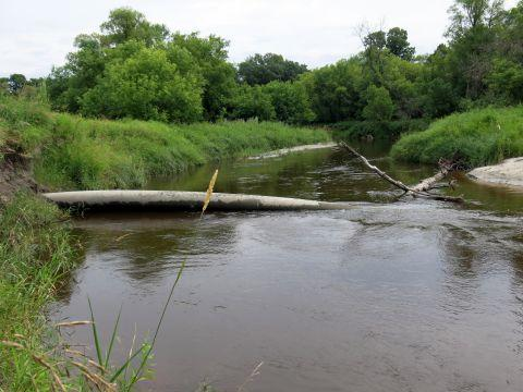 In a July 24, 2014 photo, an Enbridge crude oil pipeline is exposed by erosion on the Tamarac River in northwest Minnesota in rural Marshall County. Three of the seven lines that cross the river are exposed. Floodwater has eroded soil that once buried the pipelines several feet below ground. (AP Photo/MPR News, Dan Gunderson)