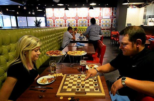 Nicole Etter, from Oakdale, and Jason Engman of St. Paul enjoy a game of checkers while also enjoying Meat'za and Breakfast Pizza at the Rival House Sporting Parlour in the DoubleTree by Hilton in downtown St. Paul on Wednesday, Aug. 14, 2014. The restaurant encourages guests to play games at the tables and bar and even provides some classics such as checkers, Connect Four and Jenga. (Pioneer Press: John Autey)