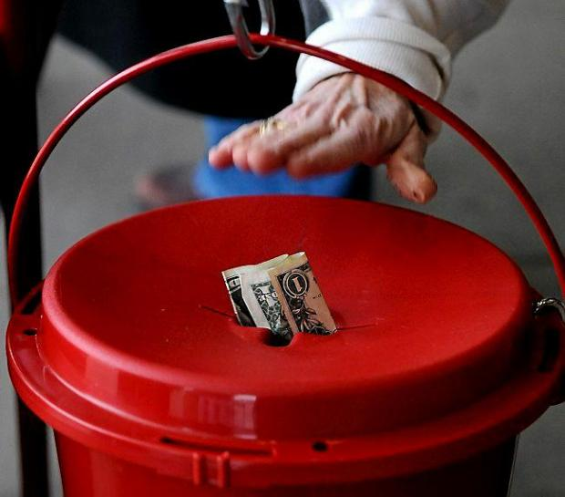 A donor taps money into a Salvation Army kettle in Hudson, Wis., on Dec. 18, 2014. (Pioneer Press: Jean Pieri)