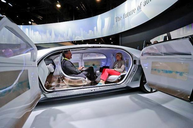 Attendees sit in the self-driving Mercedes-Benz F 015 concept car at the Mercedes-Benz booth at the International CES Tuesday, Jan. 6, 2015, in Las Vegas. (AP Photo/Jae C. Hong)