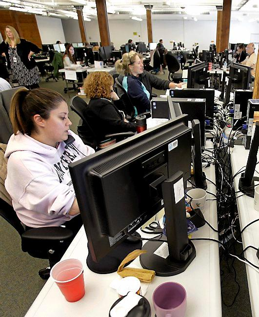 Guides work the phones in this 2013 photo in an effort to help people scrambling to finalize health coverage before the new year at Minnesota's insurance marketplace. (AP Photo/Jim Mone,File)
