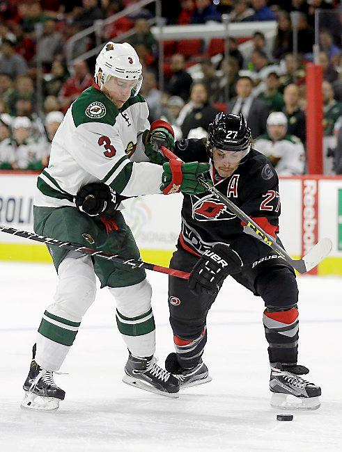 Carolina Hurricanes' Justin Faulk (27) and Minnesota Wild's Charlie Coyle (3) skate for possession of the puck during the first period of an NHL hockey game in Raleigh, N.C., Thursday, Nov. 12, 2015. (AP Photo/Gerry Broome)