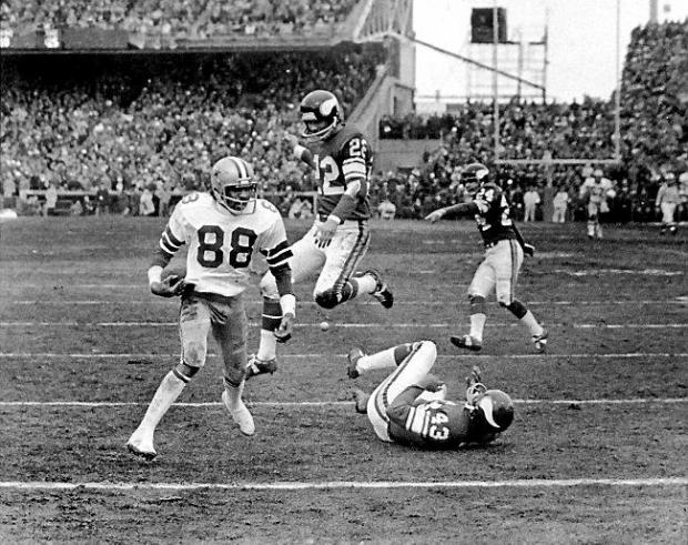 Dallas Cowboys receiver Drew Pearson walks into the end zone after catching a 50-yard TD pass from quarterback Roger Staubach during the fourth quarter of a NFC divisional playoff game at Metropolitan Stadium in Bloomington, Minn. on Dec. 28, 1975. Efforts to block Pearson by Minnesota Vikings defenders Nate Wright (43) and Paul Krause (22) were futile and Cowboys won the game 17-14. (Associated Press File)