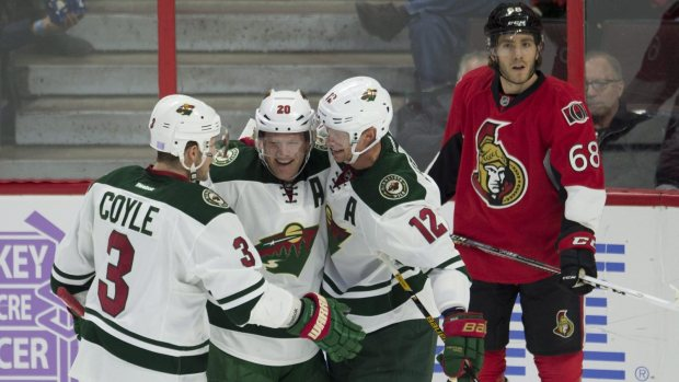 Minnesota Wild defenseman Ryan Suter, center, celebrates his goal with Eric Staal (12) and Charlie Coyle (3) during the first period of an NHL hockey game Sunday, Nov. 13, 2016, in Ottawa, Ontario. At right is Senators left wing Mike Hoffman. (Adrian Wyld/The Canadian Press via AP)