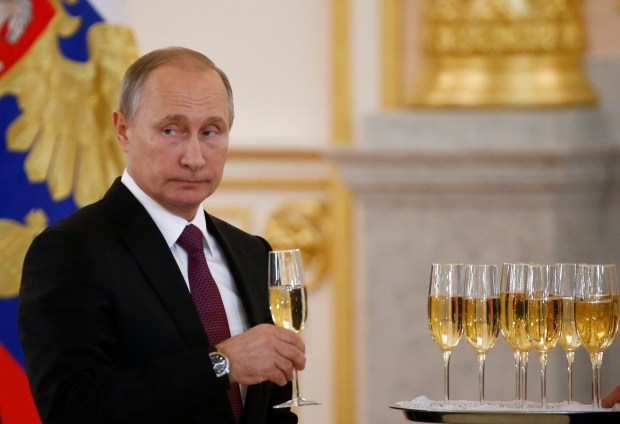 Russian President Vladimir Putin holds a glass during a ceremony of receiving diplomatic credentials from foreign ambassadors in the Kremlin in Moscow, Russia, Wednesday, Nov. 9, 2016. Putin says that Moscow is ready to try to restore good relations with the United States in the wake of the election of Donald Trump. (Sergei Karpukhin/Pool photo via AP)
