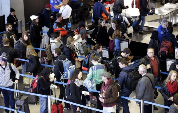 In this Sunday, Nov. 29, 2015, file photo, travelers line up at a security checkpoint area in Terminal 3 at O'Hare International Airport in Chicago.  The auto club AAA said Tuesday, Nov. 15, 2016, that it expects 1 million more Americans to venture at least 50 miles from home, a 1.9 percent increase over last year. (AP Photo/Nam Y. Huh, File)