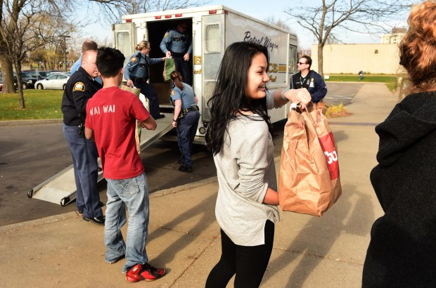 Central High School sophomore Paw Htoo passes food down the line as St. Paul police officers, Como Park High School students and Central High School students work together to supply food to the Hallie Q. Brown Community Center food shelf in St. Paul, Tuesday, November 15, 2016. The students and cops formed a human chain as they unloaded bags of food collected during a police food drive and passed them into the community center. (Pioneer Press: Scott Takushi)