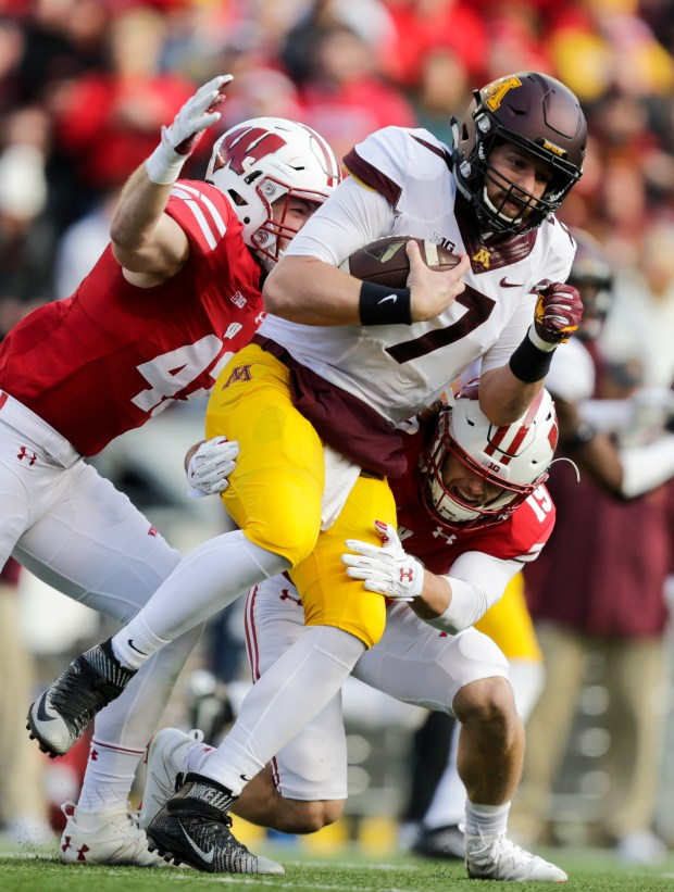 Minnesota quarterback Mitch Leidner (7) scrambles against Wisconsin linebacker Ryan Connelly, left, and safety Leo Musso and during the first half of an NCAA college football game Saturday, Nov. 26, 2016, in Madison, Wis. (AP Photo/Andy Manis)