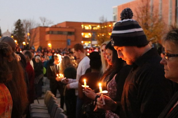 Attendees stand silently during the candlelight vigil at the memorial service of Hussain Saeed Alnahdi at the outdoor amphitheater behind the Student Memorial Center on the UW-Stout campus, Thursday, Nov. 3, 2016 in Menomonie, Wis. Police in western Wisconsin continue to look for the assailant who attacked and killed a university student from Saudi Arabia.(Marisa Wojcik/The Eau Claire Leader-Telegram via AP)