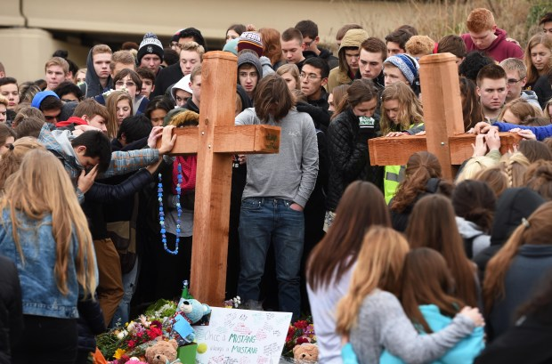 Hundreds of Mounds View High School students surround two wooden crosses Monday, Dec. 5, 2016, to remember classmates Bridget Giere and Stephanie Carlson at the crash site where the two died Thursday in Arden Hills. (Pioneer Press: Scott Takushi)