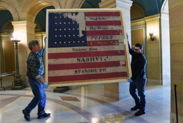 Bob Lindell, left, and Garth Thompson-Vieira move the Seventh Minnesota Volunteer Infantry Regiment's National Flag back to its display cases in the rotunda of the Minnesota State Capitol in St. Paul on Thursday, Dec. 22, 2016. This flag was the final flag used by the Seventh Minnesota during the Civil War. (Pioneer Press: Scott Takushi)