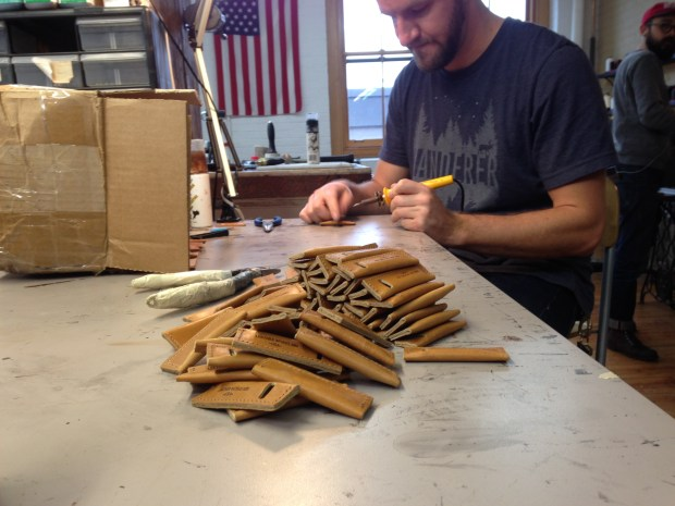 Leather Works Minnesota employee Joe Madsen puts the finishing touches on leather toothpick holders. (Richard Chin)