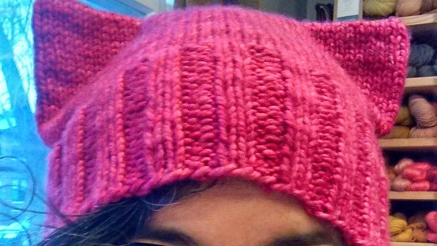 """This January 2017 photo provided by Angie Paulson, shows Paulson, a knitter who works at The Yarnery shop in Saint Paul, Minn., as she displays one of the """"pussy"""" hats she made as part of a call to action answered by thousands of knitters to supply marchers at the Women's March in Washington, D.C., on Jan. 21 with warm head gear and a way to show their solidarity for women's rights. (Angie Paulson via AP)"""