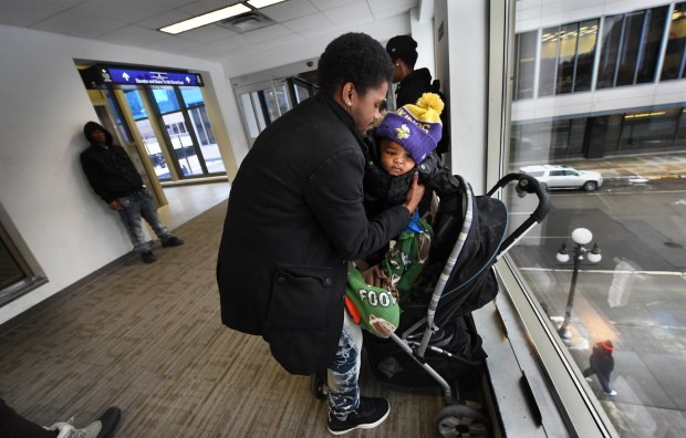 Devonte Mitchell picks up his 9-month-old baby, Geovanni, as he waits Wednesday, Jan. 25, 2017, in the skyway between the old Pioneer Press building and the Alliance Bank Center for a bus back to his shelter home in St. Paul (Pioneer Press: Jean Pieri)