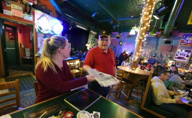 Night manager Katie Schille hands an early edition of the Pioneer Press to treasure hunter Jason Michaelson inside Shamrocks bar and grill in St. Paul, Minn., Wednesday, Jan. 25, 2017. (Pioneer Press: Dave Orrick)