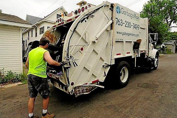 Daniel Westerhaus, a partner in a GarbageMan franchise, picks up trash from an East Side neighborhood in St. Paul on August 21, 2013. (Pioneer Press: Scott Takushi)