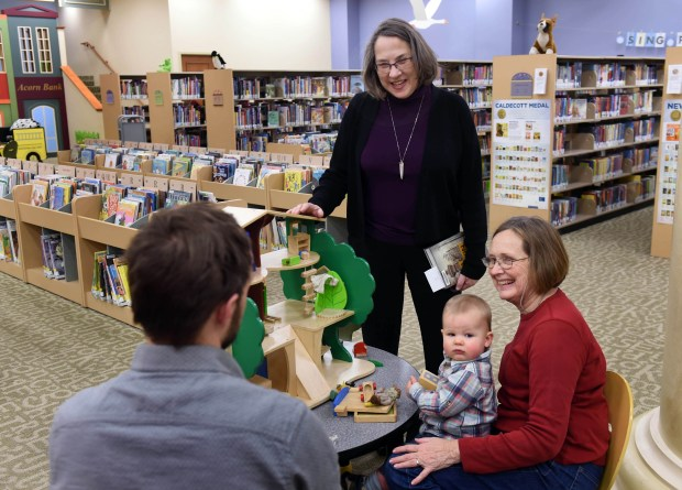 Lynne Bertalmio, center, chats with Mike Prince, left, of Seattle and his mother, Nancy Prince of Stillwater, who holds granddaughter Charlotte, at the Stillwater Public Library on Tuesday, Feb. 7, 2017. Bertalmio is retiring after 42 years as director of the Stillwater Public Library. (Pioneer Press: Scott Takushi)