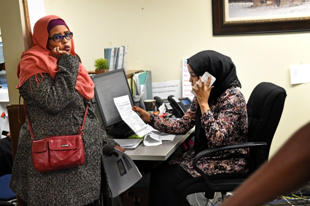 Hodan Ahmed, left, waits for Munira Mohamed to call the MNsure helpline to get Hodan's password and user name during sign up for MNsure at Briva Health offices in Minneapolis on the last day before an enrollment deadline on Wednesday, Feb. 8, 2017. (Pioneer Press: Jean Pieri)