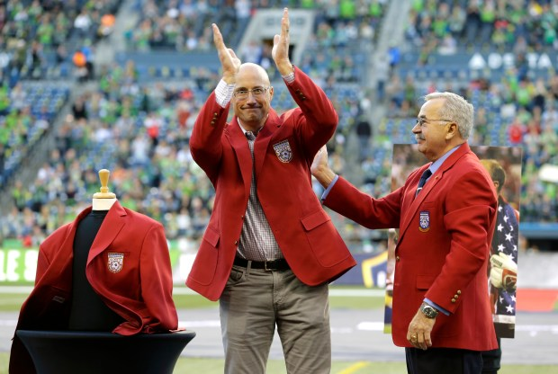 Former Seattle Sounders goalkeeper Kasey Keller, left, is honored with a red jacket presented by Hank Steinbrecher, right, of the U.S. Soccer Hall of Fame, Sunday, Oct. 4, 2015, before an MLS soccer match between the Sounders and the Los Angeles Galaxy, in Seattle. Keller was officially inducted into the Hall of Fame during a ceremony on Saturday. (AP Photo/Ted S. Warren)