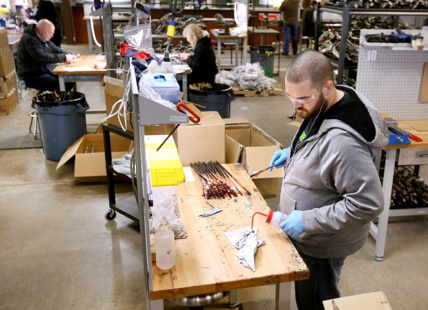 Cory Townsend, production worker, assembles arrows for new Ravin crossbows at the Ravin manufacturing facility in Superior. (Bob King / rking@duluthnews.com)