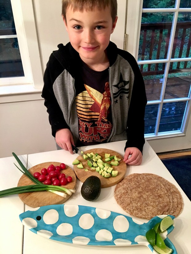 Josh Adams, 7, slices avocados for a fish taco buffet. (Courtesy of Donna Erickson)