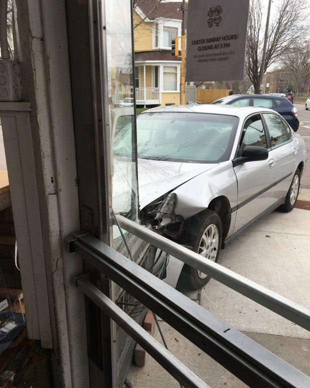 A car rests against the wall of Groundswell coffee shop Thursday, April 13, 2017, after a two-car collision at the corner of Thomas and Hamline avenues. No one was injured but the coffee shop had to close for clean up and repairs. (Courtesy of Megan Greulich)