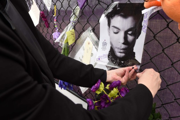 Michele Brambilla of Shakopee attaches a photo with a personal note on the Prince4Ever Tribute Fence at Paisley Park, the late Prince's home and studio, in Chanhassen on Monday, April 10, 2017. (Scott Takushi / Pioneer Press)