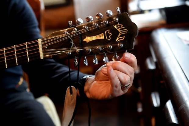 Wood tunes his guitar before practicing in his home office. Before Wood turned to writing, he was a musician and still is. (Jean Pieri / Pioneer Press)