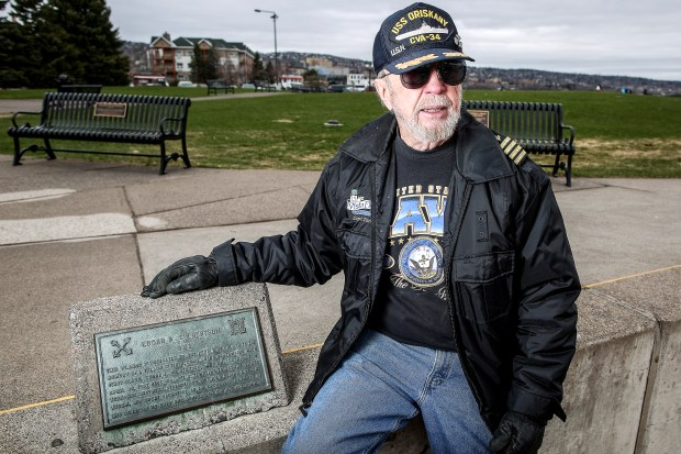 Tom Mackay was a friend of Edgar Culbertson, the Coast Guard member who drowned, and sits by a plaque honoring him in Canal Park. (Clint Austin / caustin@duluthnews.com)
