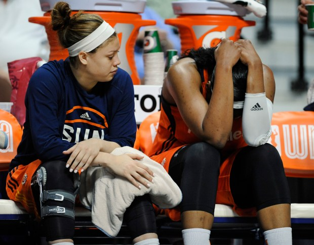 Connecticut Sun's Kelsey Bone, right, holds her head after a hard fall on the court as teammate Rachel Banham, left, looks on during the first half of a WNBA basketball game against the San Antonio Stars, Sunday, June 19, 2016, in Uncasville, Conn. (AP Photo/Jessica Hill)