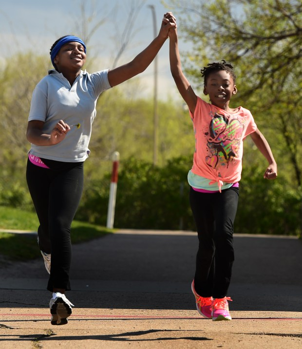 Fifth-grader Desire Negron, left, and third-grader Kennedy Greer hold hands as they run a lap with the Girls on the Run club after school at Maxfield Elementary School in St. Paul on Wednesday, May 3, 2017. Girls meet weekly for 90-minute practices during the clubÕs fall and spring seasons to run together and learn about what it means to be healthy, skillful and confident members of the community. (Scott Takushi / Pioneer Press)