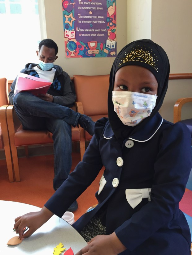 In this Tuesday, May 2, 2017 photo, Amira Hassan,of Burnsville, Minn., plays in the waiting room at the specialty clinic at Children's Minnesota in Minneapolis, while her dad, Mohamud Hassan, fills out paperwork. The girl went to the hospital's clinic for a routine wellness check, but she and her father both had to wear a mask to protect them from measles after an outbreak has sickened more than 30 children in Minnesota. The masks are just one precaution that hospitals are taking to try to control the spread of the disease, which is predominantly affecting Minnesota's Somali community. (AP Photo/Amy Forliti)
