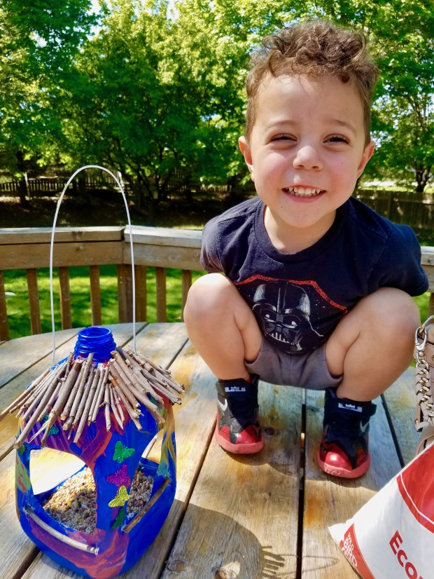 Jameson Whitfield, 3, and his milk-jug bird feeder he painted and decorated to hang in his back yard. (Courtesy of Donna Erickson)