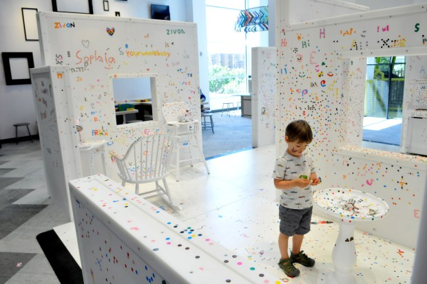 """Arlo Schneiders, 3, says """"I like putting stickers on furniture. I'm making the house more beautiful. """" Arlo was decorating in the Creativity Jam, one of 10 new exhibits at the Minnesota Children's Museum. The facility officially reopens Wednesday. (Ginger Pinson / Pioneer Press)"""