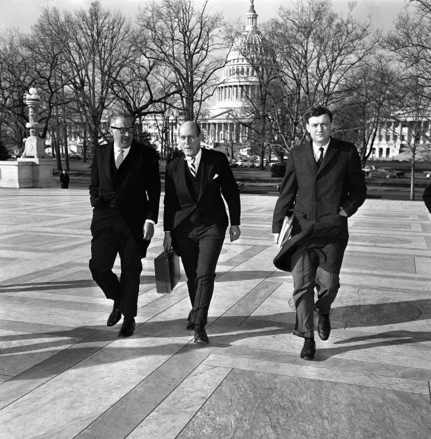 Attorney General Nicholas Katzenbach, center, is accompanied by Solicitor General Thurgood Marshall, left, and Asst. Atty. Gen. John Doar as he arrives on Jan. 17, 1966 at the Supreme Court in Washington to defend the legality of the 1965 Voting Rights Act. At issue is whether the federal government has the constitutional authority to abolish literacy and other voter qualifications which had been required in some states. The law is challenged by six southern states. The U.S. Capitol Building is in the background. (AP Photo)