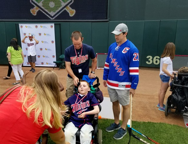 Jeffrey Bergeman, 11, of Chippewa Falls, Wis., and his father, Jordan, spend some time with New York Rangers captain Ryan McDonagh at the second annual Mauer and Friends Kids Classic at Target Field in Minneapolis on Friday, June 16, 2017. Bergeman, who was diagnosed with cerebral palsy after suffering a cardiac arrest at 22-months-old, was one of more than 20 patients and their families from Gillette Children's Specialty Healthcare who spent time on Target Field with dozens of sports celebrities. (Lina Abdennabi / Gillette Children's Specialty Healthcare)