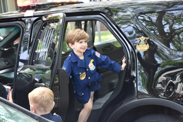 Miles Westra, 5, got to take a look at the inside of St. Paul Police Officer Heather Gustafson's squad vehicle after Gustafson and her partner, Officer Charlie Busch, stopped by his birthday party in the Mac-Groveland neighborhood of St. Paul, Minn. on Saturday, June 3, 2017. (Will Ashenmacher/Pioneer Press)
