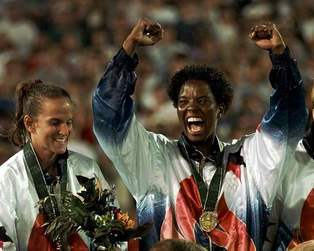 Carla Overbeck, left, and Briana Scurry of the U.S. Olympic women's soccer team react during the gold medal ceremony Thursday, Aug 1, 1996 at Sanford Stadium in Athens, Ga. The U.S. beat China 2-1 to win the first ever medal awarded in women's soccer at an Olympic Games.(AP Photo/Luca Bruno)