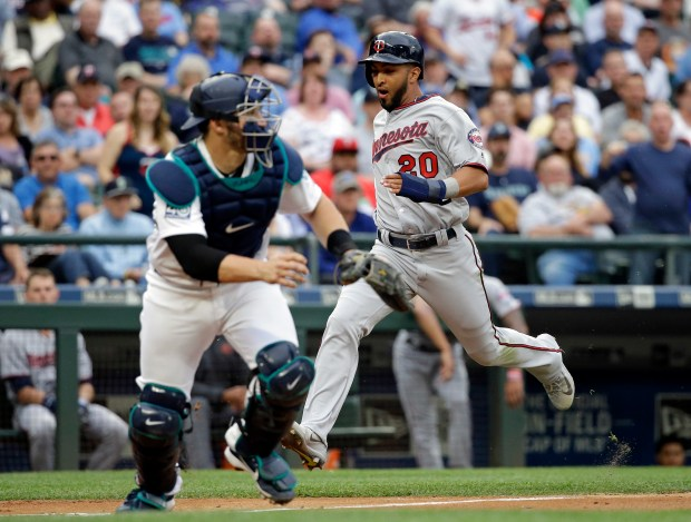 Minnesota Twins' Eddie Rosario (20) scores as Seattle Mariners catcher Mike Zunino waits for the ball during the third inning of a baseball game Wednesday, June 7, 2017, in Seattle. (AP Photo/Elaine Thompson)