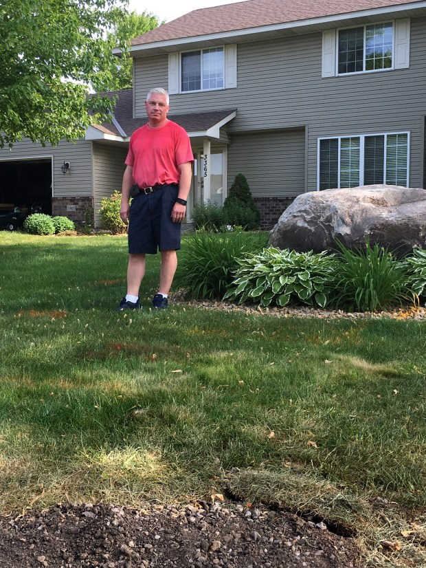Tom Erickson surveys the spray-paint stripes that mark the boundaries of a planned multi-use trail that will be built across the front lawn of his Woodbury home on Friday, June 9, 2017. City officials plan an eight-foot-wide asphalt trail on a right-of-way easement that will provide a link between a city pathway and a walking trail to Red Rock Elementary School. (Bob Shaw / Pioneer Press)