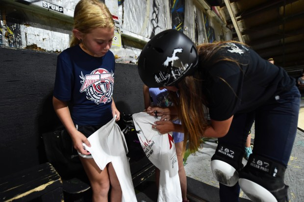 Stillwater's Nicole Hause signs a t-shirt for sisters Skylar Hofer, 9, and Willow, 6, (partially hidden) at the 3rd Lair Skate Park in Golden Valley, Monday, July 10, 2017. Hause will be one of eight women competing this Saturday in the Women's Park event at the X Games, which start Thursday at U.S. Bank Stadium in Minneapolis. (Scott Takushi / Pioneer Press)