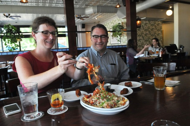 Vanessa Perry, left, serves up some bacon and cheese fries to her husband, Travis Snider, during Happy Hour at Augustine's Bar and Bakery on Friday, July 21, 2017. The couple live in the neighborhood and were taking a break from the dissertation that Perry is working on. Augustine's Bar Happy Hour is from 3-6 pm daily. (Ginger Pinson / Pioneer Press)