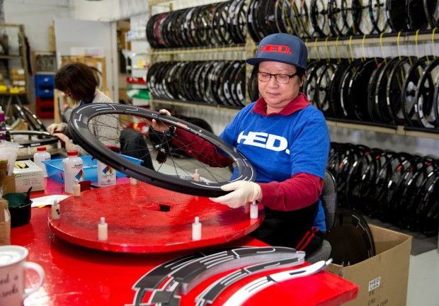 Mara K, an employee at Hed Cycling, applies rim decals to a wheel being built at the company's production facility in Roseville in an undated courtesy photo, circa July 2017. Anne Hed, who started the company with her late husband, Steve, in 1984, has been running Hed Cycling as the sole owner since Steve's sudden death in 2014. The company started with bike wheels and for the past few years, Hed Cycling has been making bike frames, too. You won't see any of Hed Cycling's frames in the Tour de France -- they're primarily for triathletes -- but you will see their wheels. Four teams, comprised of nine cyclists, are using Hed Cycling wheels in this year's Tour de France time trials. (Courtesy of Brian Ach / Hed Cycling)